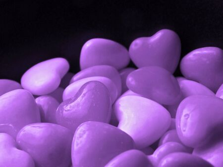 Purple candy hearts piled high against black background.