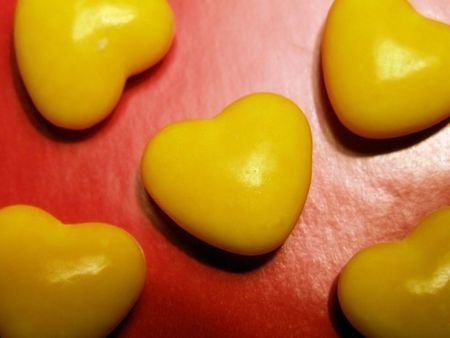 profesar: Amarillo caramelos duro en la reflexi�n de fondo rojo.