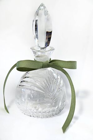Glass crystal perfume bottle with ribbed sage or heather green ribbon tied in a bow set on a white background