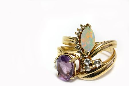 Two rings displayed stacked, one opal with diaminds, the other Amethyst. Both in gold settings on white background. Stock Photo - 7578483