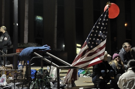 demonstrators: San Diego, California, USA, November 21, 2011: The Stars and Stripes stand in a railing along side Occupy San Diego demonstrators at the Civic Center in San Diego