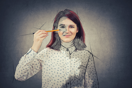Young smiling student girl businesswoman, holding a pencil pointed to his face trying to draw a sketch of her emotion. Create yourself idea, self development concept isolated on grey wall background.