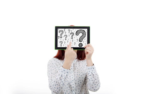 Portrait of confused, thinking young businesswoman seeks a solution, covering her face using a digital tablet with drawn question marks on the display, isolated on white background.