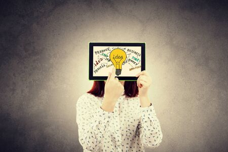 Portrait of thinking young businesswoman seeks a solution, having ideas, covering her face using a digital tablet with drawn business sketches on the screen, isolated on grey wall background.