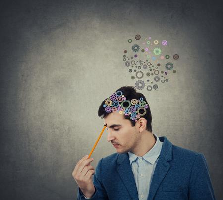 Jonge man denken en op zoek naar de juiste versnelling voor de vorming van een complete hersenen. Het vinden van de juiste oplossing concept. Stockfoto