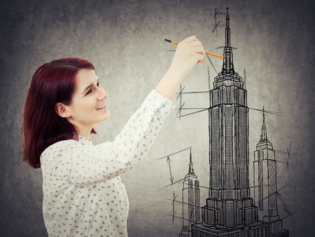 architect drawing: Young woman architect sketching a construction project, the exterior of a skyscraper. Architectural drawing concept. Tall building business center plan isolated on grey background.