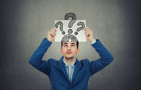 Portrait of confused, thinking young businessman seeks a solution looking up, holding a paper over head with drawn question marks, isolated on gray wall background. Human face expression.