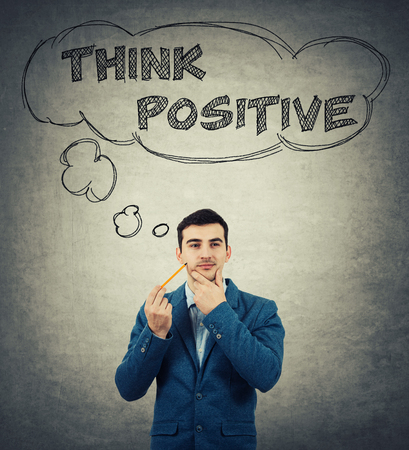 appearance: Young businessman, holding a pencil pointed to face, drawing thought bubbles over head. Think positive concept isolated on grey wall background. Stock Photo