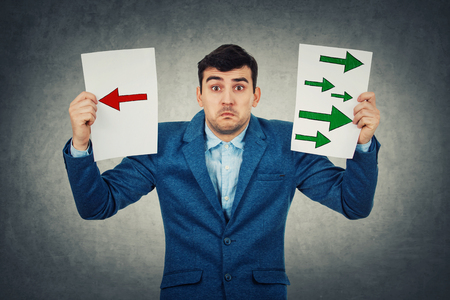 Confused young businessman holding two sheets with drawn arrows poinded to the left and right side. Undecided boy try to choose between two directions. Business decision and choice symbol., life perception concept.
