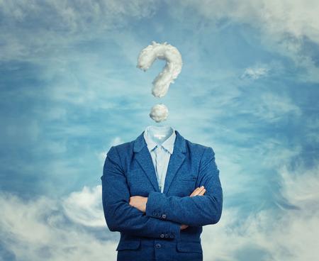 Surrealistisch beeld als een zakenman met een onzichtbaar gezicht met gekruiste handen en vraagteken in de plaats van zijn hoofd, als een masker, om zijn identiteit te verbergen. Ondervragingsteken symboliseert het hoofd in de wolken, geïsoleerd op blauwe hemelachtergrond. Stockfoto
