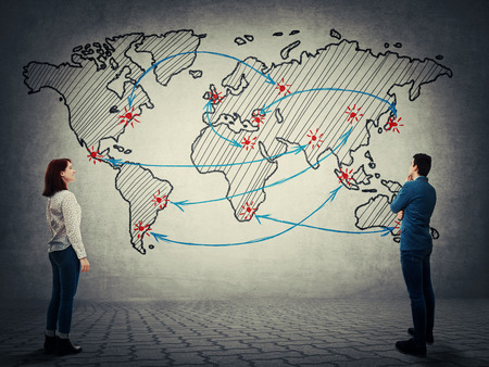 Businessman and woman stand in front of the world map. Business trade, distribution and globalization concept.