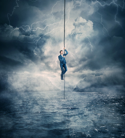 Businessman salvation, surviving the storm buiness concept as a scared man hanging on a chain above the ocean water, trying to climb up. Risk symbol, metaphor for conquering adversity and overcoming challenges. Stock Photo