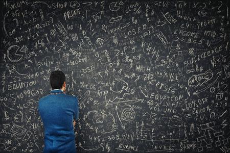 La vista posteriore di un uomo d'affari perplesso davanti a un'enorme lavagna tenta di risolvere calcoli, formule ed equazioni matematiche difficili. Pensando alle idee di progetto e al concetto di pianificazione aziendale.