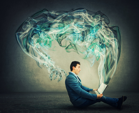 Surprised businessman sitting on the floor looks at his laptop as dark smoke comes out of the monitor as technology monster with big claws trying to scare. Negative influence of the virtual world.