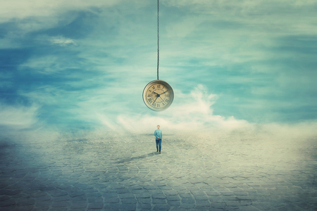 Surreal view as a man walking on a pavement road and a suspended clock on his back hanging from the sky. The importance of time in the modern world. Time travel concept.
