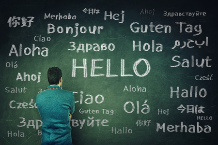 Rear view of a puzzled businessman in front of a huge chalkboard written with the word hallo in different languages. Opportunity for learning new languages for students. Banque d'images
