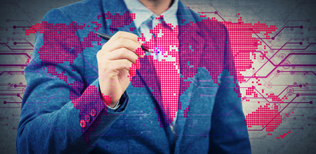 Businessman with a pen select a point on a digital world map hologram. Choosing the right place for business development. Virtual technology and cryptocurrency security concept. Double exposure.