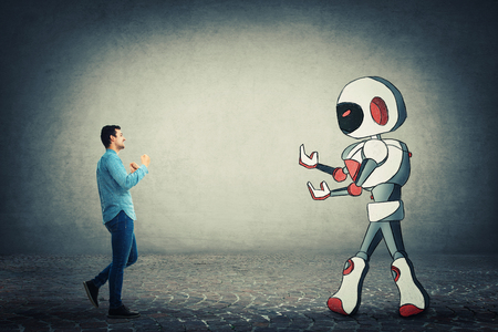 Young businessman holding fists ready to fight against robot. Rivalry between human and technology. Danger of losing the job, replacing the human work force with the robotic. Artificial intelligence.