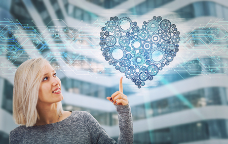 Portrait of smiling woman pointing finger up showing a gear heart hologram. Future technology artificial intelligence health protection. Human character and emotions concept. Choose with your heart.