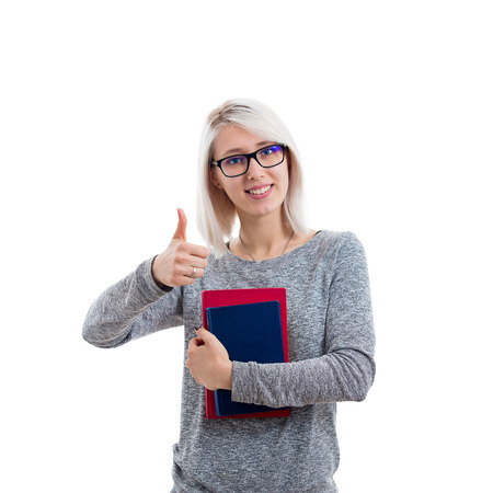 Portrait of a smiling pretty student girl wearing glasses and holding books isolated over white background.