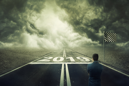 Surreal view as a competitive young businessman stand on the road in front of the start line with numbers 2019. Business challenge and motivation for a new year. Opportunity way, development concept. Stock Photo