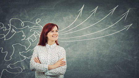 Concept of information processing as a concentrated redhead woman smiling in front of a huge blackboard as mesh lines come through head and transform into straight arrows as project ideas. Stock Photo