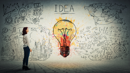 Side view of a pensive young woman looking at the wall with colorful light bulb and business sketch. Uniqueness of the idea and genius concept.