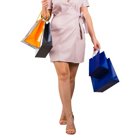 Girl walking and carrying shopping bags. Woman legs close up isolated on white background.