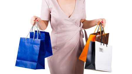 Close up of a woman body waist with hands holding shopping bags isolated over white background.