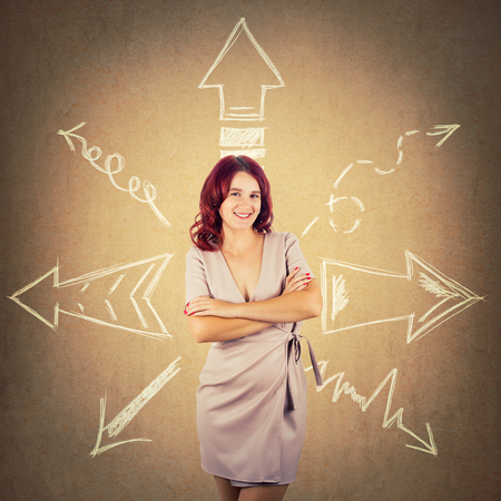 Redhead woman standing with arms crossed and arrows pointed to different directions over colorful background. Difficult choice, decide which way to go.