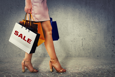 Close up of woman legs high heel shoes walking and carrying shopping bags on sale season isolated over concrete grey wall background. 写真素材