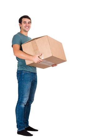 Full length portrait of smiling young man carrying a big cardboard box, worder shipping isolated over white background. Stock Photo
