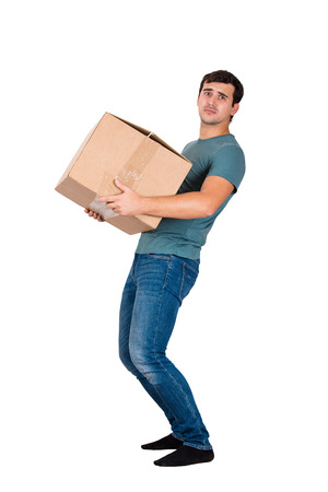 Frustrated young man lean back carrying a heavy box isolated on white background. Package delivery full length portrait