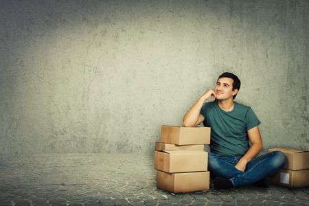 Pensive young man sitting and leaning on cardboard boxes hand on cheek and dream. Ready for moving to a new house over grey wall background.