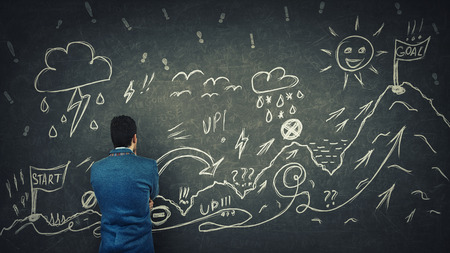 Rear view of a puzzled businessman having questions in front of a blackboard to cross the difficult quest way with obstacles. Imagens