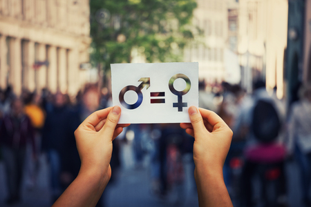 Gender equality concept as woman hands holding a white paper sheet with male and female symbol over a crowded city street background.