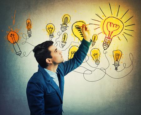 Thoughtful businessman drawing imaginative shining light bulbs. 版權商用圖片