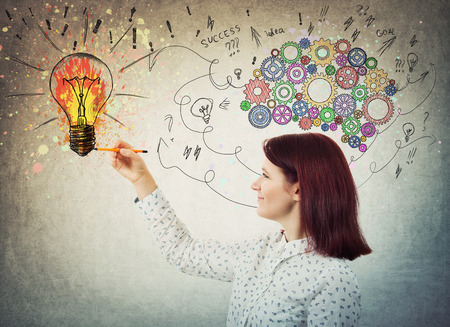 Young woman with colorful gear brain above head, positive emotion, drawing a genius idea as arrows and curves going to a color splash light bulb.