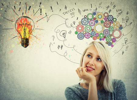 Young woman hand under chin and colorful gear brain above head. Pensive emotion, positive thinking with arrows and curves going to a colorful light bulb.