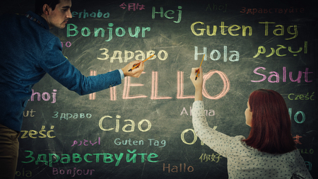 Man and woman together drawing word hello in different languages and colors on blackboard. Stok Fotoğraf