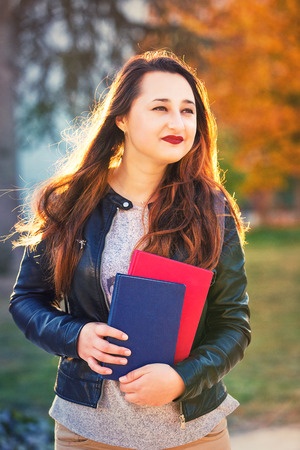Thoughtful young woman student holding books looking away over colorful autumn trees background.