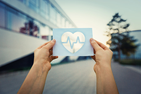 Close up of woman hands holding a paper sheet with the heart beating symbol inside, over hospital building background.