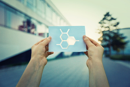 Close up of woman hands holding a paper sheet with scientific cell structure symbol inside, over laboratory building background.