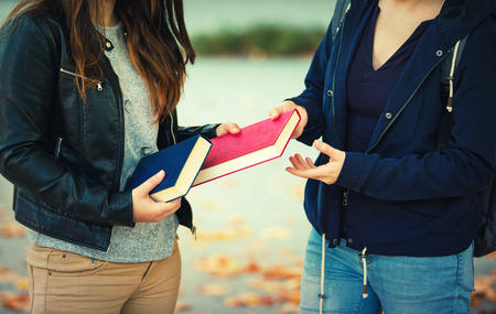 Close up outdoors portrait of two women students exchanging books.