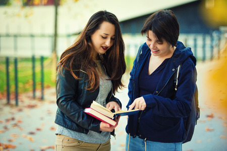 Two cheerful young women students pointing finger to a book finding the correct answer for their question. 版權商用圖片