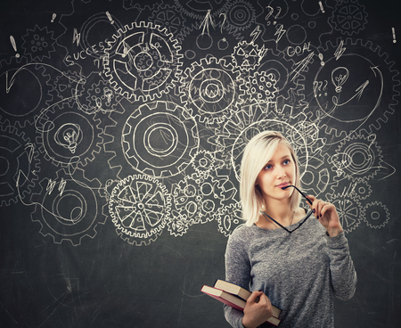 Hard thinking serious smart woman holding books over blackboard background gear brain arrows and mess as thoughts. Concept for mental, psychological development. Finding solution to problem.