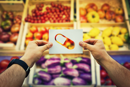 Hands holding a paper sheet with vitamins supplement capsule over market shelves background with fresh fruits and vegetables. Nutrition pill as as natural medicine health treatment.