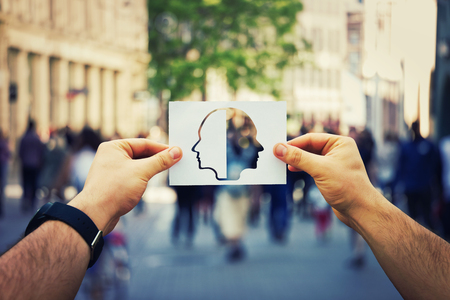 Man hands holding a white paper sheet with two faced head over a crowded street background. Split personality, bipolar mental health disorder concept. Schizophrenia psychiatric disease.