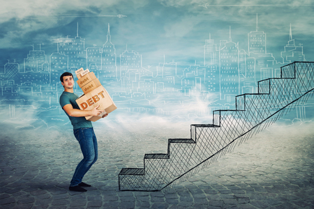 Frustrated young man too much burden, lean back carrying heavy boxes with debt word text, have to climb a staircase. Concept of difficult life road, a lot of credits and taxes to pay. Stock Photo