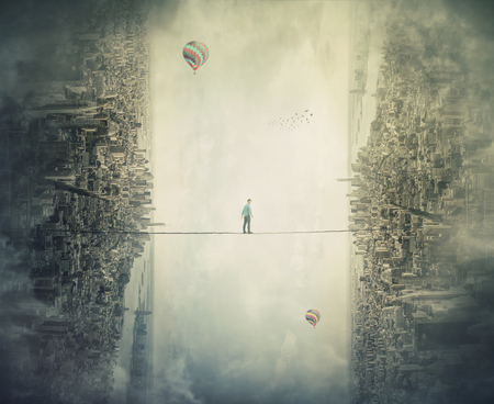 Young man silhouette balancing on slackline rope high above clouds between two imaginary parallel worlds. Slackliner walking on tightrope looking down scared. Conquering metaphor, overcome challenge. Imagens